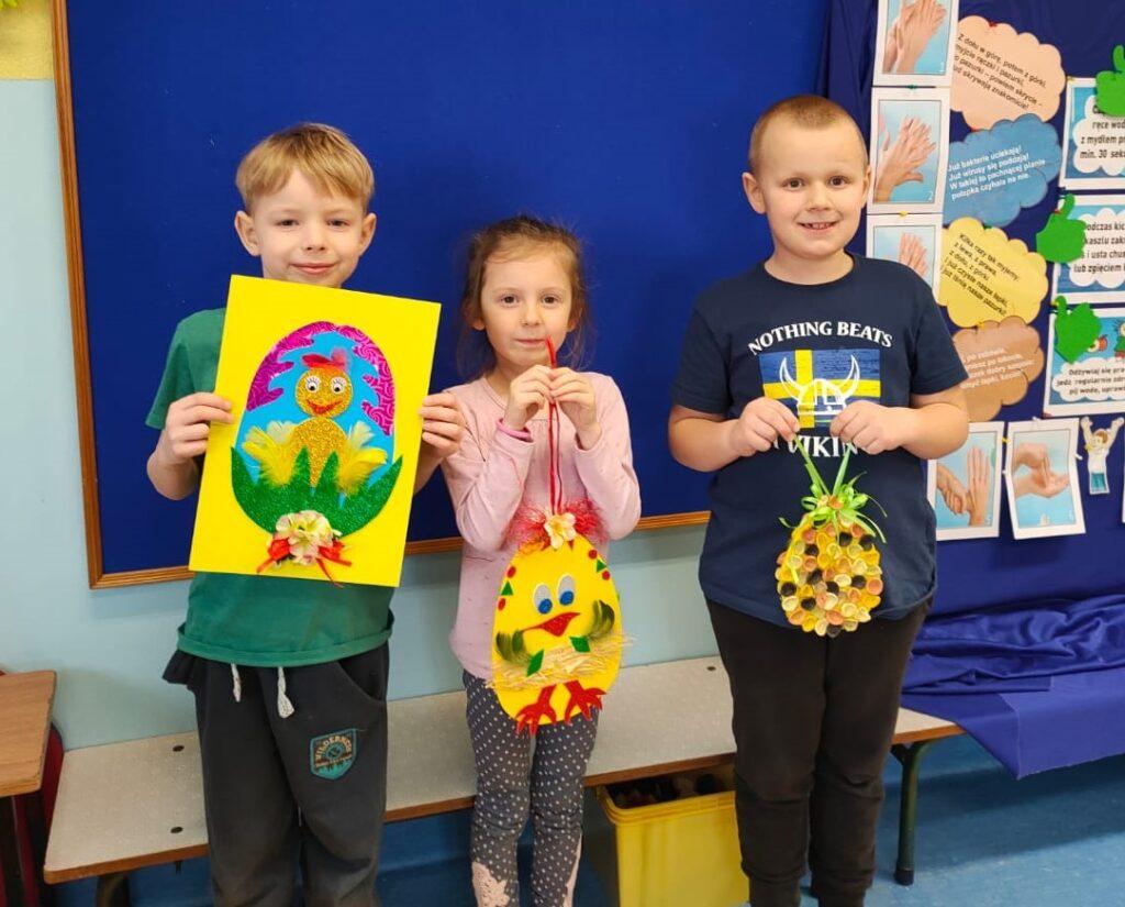 Dzieci prezentujące swoje prace plastyczne.